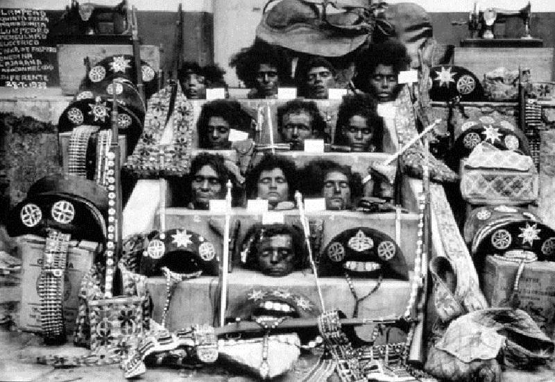 Fotografia icônica mostra as cabeças de Lampião (última de baixo), Maria Bonita  (logo acima de Lampião) e outros cangaceiros do bando.