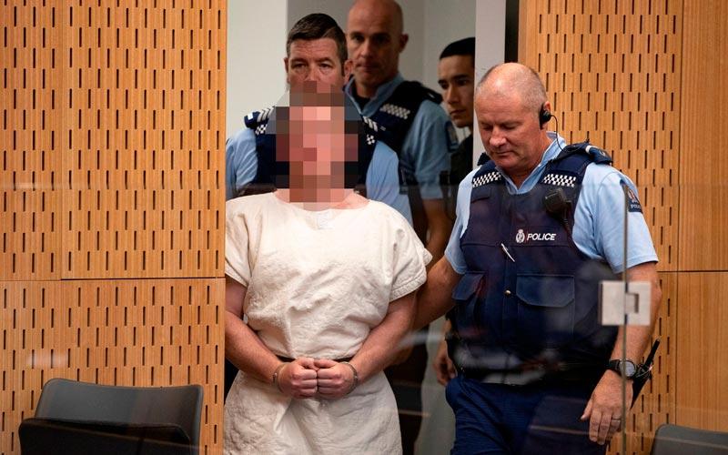 Brenton Tarrant é acompanhado por policiais durante sua apresentação à corte do Distrito de Christchurch, na Nova Zelândia, no sábado (16)